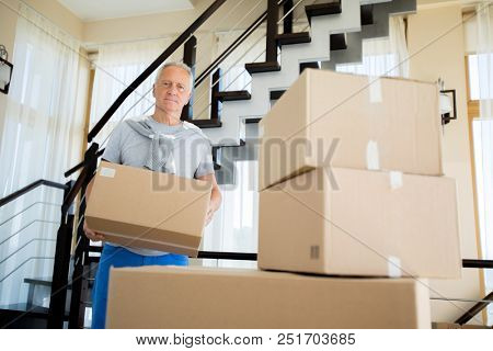 Portrait of senior man holding cardboard box posing in new house and looking at camera, copy space