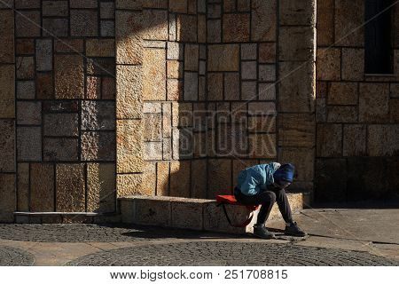 Unidentifiable, Poor Child Sits Alone And Sad On The Street On A Cold Day. Hopeless Unrecognizable Y