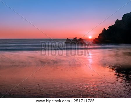 Long-exposure Photography Of Jagged Coastal Rocks On The Pacific Coast At Sunset. A Low Angle Shot T