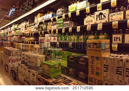 Various Selection Of Beer Bottles On Display At Supermarket
