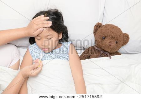 Sick Girl With Thermometer Laying On Bed