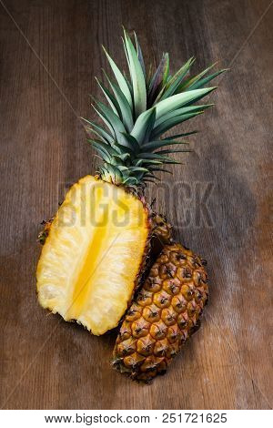 Pineapple Fruit Cut Half Displayed On Wooden Background. Juicy Organically Grown Ripe And Sweet