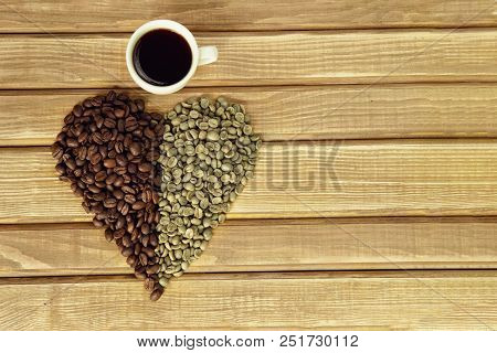 Heart Of Fried And Green Coffee Beans, A Cup Of Coffee On Wooden Background. Copy Space
