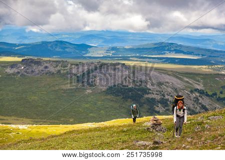 Atmospheric Moment In Mountains. Hiking Women With Backpack Traveler On Top Of Mountains. Stylish Wo
