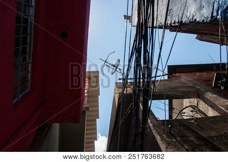 Low Angle Photo Ofl Worn Houses And Wires Of A Favela In Brazil.