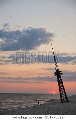 Colorful Dawn Over The Sea. Abandoned Rusty Tower On The Beach