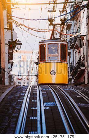 Lisbon's Gloria Yellow Funicular Drives Down The Street. Lisbon, Portugal. West Side Of The Avenida