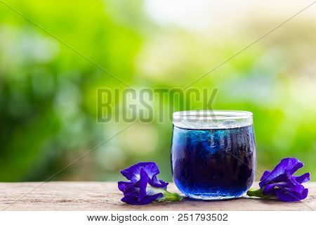 Fresh Purple Butterfly Pea Or Blue Pea Flower And Juice In Glass On Wooden Table Background
