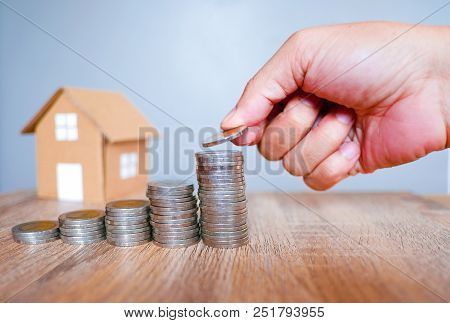 Five Of Coins Stack With Human Hand On Wooden Table And House Model Against Gray Background For Savi