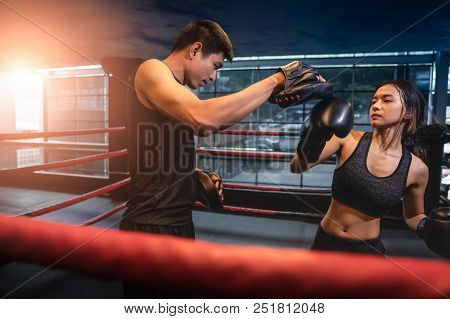 Young Adult Woman Doing Kickboxing Training With Her Coach.