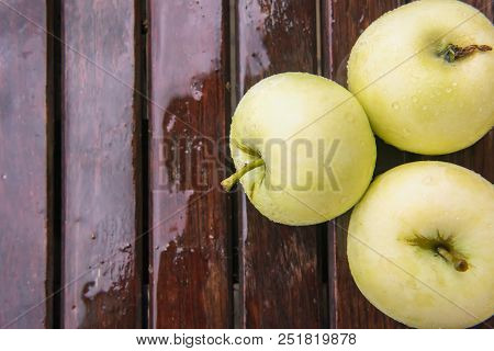 Close-up Of Few Wet Golden Green Apples Covered By Water Drops On Brown Wet Natural Old Wooden Table