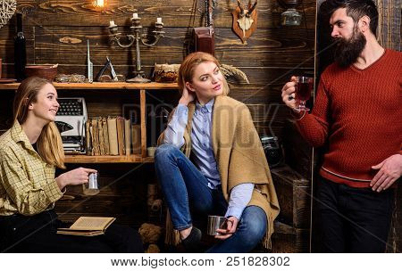 Friends, family spend pleasant evening, interior background. Family enjoy vacation in gamekeepers house. Coziness concept. Girls and man on happy faces hold metallic mugs, enjoy coziness with drinks. poster