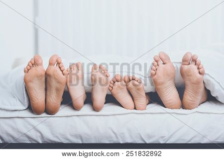 Close Up Family In Bed Under Cover Showing Feet. Family Concept.