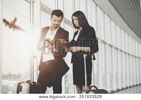 Business Woman And Man Holding Tickets In Airport. Checking Tickets While Aircraft Flying. Airport,