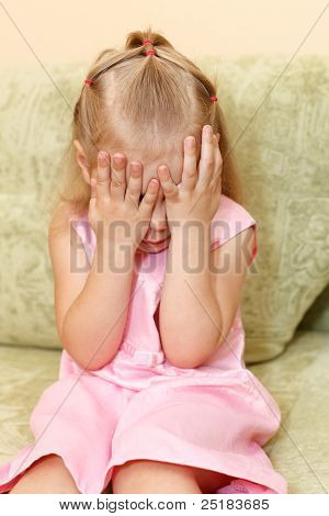 Little child a girl in pink dress sitting on sofa in domestic room and closes face by hands. poster