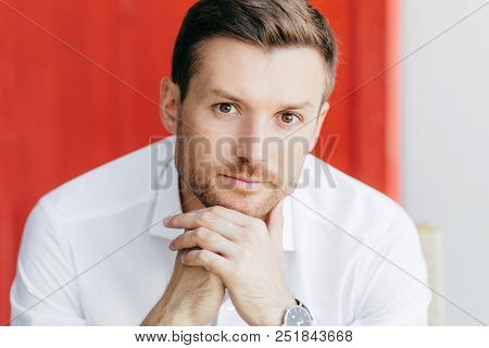 Indoor Shot Of Pensive Young Male Office Worker Keeps Hand Together Under Chin, Wears White Shirt, L