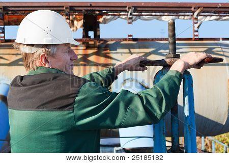 Manual worker turning big valve