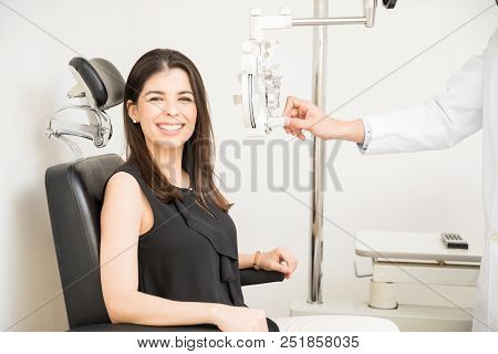 Portrait Of Happy Young Woman Sitting Behind Phoropter During Eye Exam While Looking At Camera And M