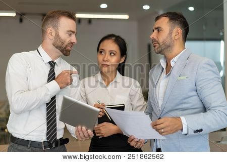 Confident Businessman Presenting His Strategy To Colleagues. Ambitious Interracial Team Members Disc