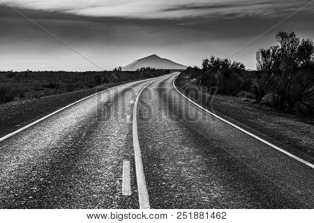 Rural Road In South Australian Outback Leading To A Beautiful Mountain Peak In Black And White