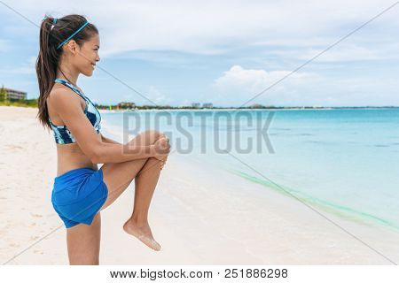 Fitness runner woman doing body warm-up stretch exercise on beach before running, stretching leg quad muscles with standing single knee to chest. Female athlete preparing legs for cardio workout.