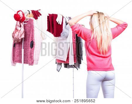 Young Woman Standing In Wardrobe Or In Mall Shop, Choosing Warm Clothes, Deciding What To Wear Or Bu