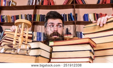 Teacher Or Student With Beard Sits At Table With Books, Defocused. Man On Frightened Face Between Pi