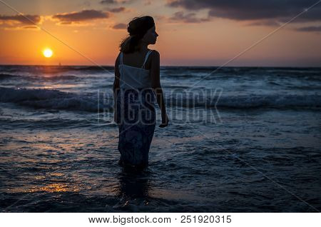 A Beautiful Caucasian Girl In A Long Dress In The Sunset Over The Mediterranean Sea.
