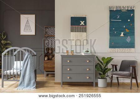 Real Photo Of A Grey Cupboard Standing Between A Crib, And An Armchair And Plant In Spacious Child's