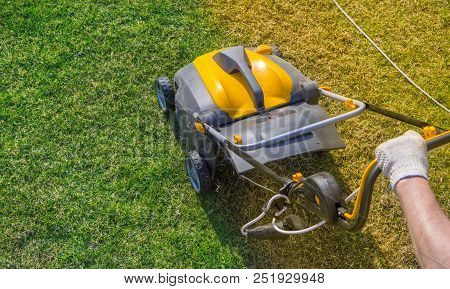 Aeration Of The Lawn In The Garden. Yellow Aerator On Green Grass Close Up