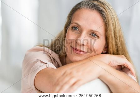 Smiling senior woman sitting on couch and thinking about her new idea. Portrait of pensive lady relaxing at home and looking away. Closeup face of mature woman planning her future on sofa.