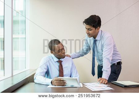Focused New Employee Consulting Mentor About Data On Tablet Screen. Standing Indian In Formal Wear P