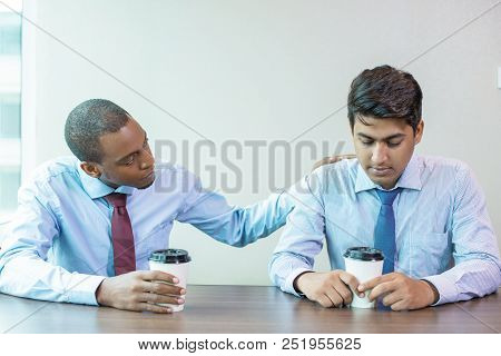 Sad Business Colleagues Discussing Bad News During Coffee Break. Afro American Employee Expressing S
