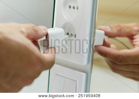Hand inserting unplug or plugged electrical plug into outlet poster