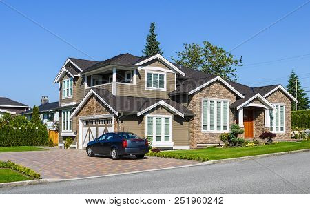 Luxury Residential House With Green Hedge On Side And Green Lawn In Front. Suburban Family House Wit