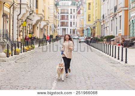 The Woman Take A Walk With Husky Dog At Sunny Autumn Day On Old European City Street. Horizontal Vie
