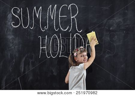 Schoolgirl Standing In Front Of A Chalkboard And Wiping Summer Holidays Inscription From It With A S