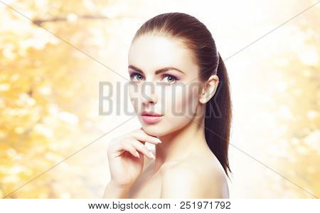 Portrait of young, natural and healthy woman over yellow autumn background.