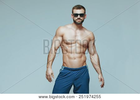 Bodybuilder Posing. Beautiful Sporty Guy Male Power. Fitness Muscled In Blue Shorts And Sunglasses.