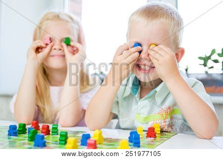 Little Blonde Girl And Boy Have Fun, Laugh And Indulge Playing Board Game. Hold People Figures In Ha
