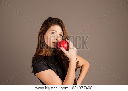 Portrait Of A Fashionable Elegant Girl In A Black Dress With Red Apple On A Dark Background. Evening