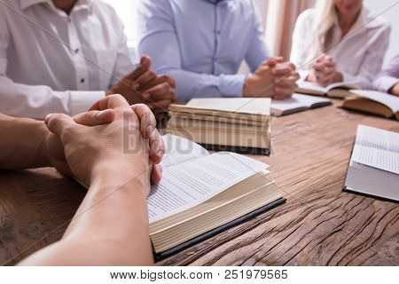 Close-up Of A Man Praying Hand On Bible Over Wooden Desk