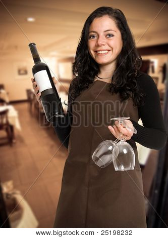 Smiling female sommelier presenting a wine bottle with a blank label and a pair of glasses in a restaurant
