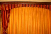 Orange drapery with red curtains made from velvet poster
