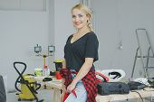 Gorgeous young blond female in beautiful casual clothes standing leaning on top of carpenter workbench in workshop smiling and looking at camera poster