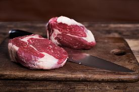 Two Raw Rib-eye Steaks With Knife On Wooden Background