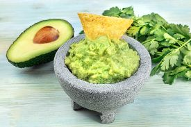 A Photo Of Guacamole Sauce In A Molcajete, Traditional Mexican Mortar, On A Teal Background, With A