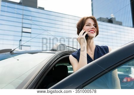 Business Woman With Red Lips In A Suit Gets Out Of The Car And Talks On The Phone.
