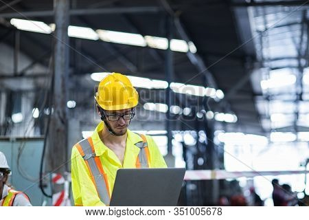 Men Industrial Engineer In Uniform And Wearing A Yellow Helmet While Standing In A Heavy Industrial