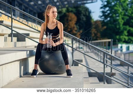 Young Sports Woman In Stylish Black Sportswear Holding Bottle Of Water In Hand While Sitting On Fitn